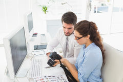 Concentrated coworkers holding digital camera Royalty Free Stock Photos