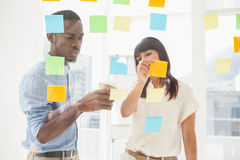 Concentrated coworkers looking at sticky notes Royalty Free Stock Photo