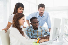 Concentrated coworkers using computer together Royalty Free Stock Image