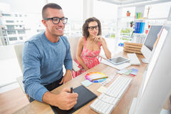 Concentrated coworkers using laptop and digitizer Royalty Free Stock Photos