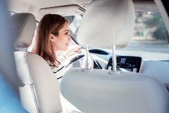 Concentrated cute woman sitting in the car and looking aside. Full concentration. Concentrated cute responsible woman sitting in the car holding by the helm and royalty free stock photos