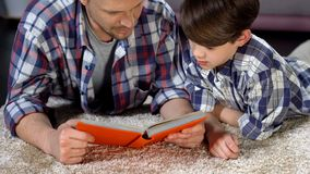 Concentrated dad and son reading interesting encyclopedia for boys, education. Stock photo royalty free stock photo