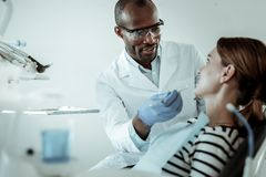 Concentrated dark-skinned doctor curing his female patient teeth stock photography