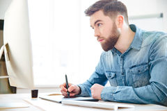 Concentrated designer drawing using computer and graphic tablet. Concentrated handsome young designer with beard in blue shirt drawing using computer and graphic Royalty Free Stock Photography