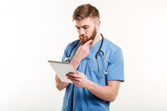 Concentrated doctor or nurse thinking while looking at tablet computer Stock Photos
