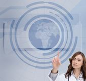 Concentrated doctor pointing at holographic globe Stock Images
