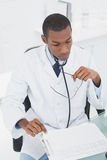 Concentrated doctor reading a note at medical office Royalty Free Stock Photos