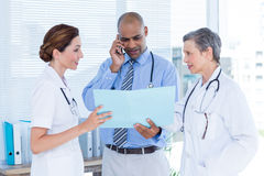 Concentrated doctor showing file to his colleagues while calling Stock Photo