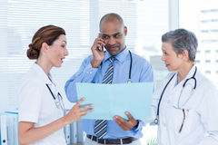 Concentrated doctor showing file to his colleagues while calling Royalty Free Stock Image