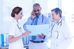 Concentrated doctor showing file to his colleagues while calling Royalty Free Stock Photos