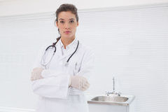 Concentrated doctor standing with stethoscope Royalty Free Stock Photos