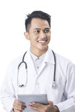 Concentrated doctor with tablet Stock Photography