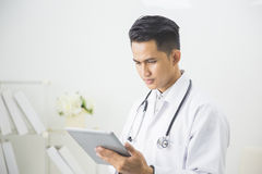 Concentrated doctor with tablet Royalty Free Stock Images