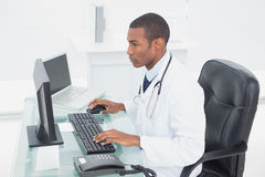Concentrated doctor using computer at medical office Stock Image