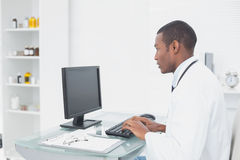 Concentrated doctor using computer at medical office Royalty Free Stock Photography