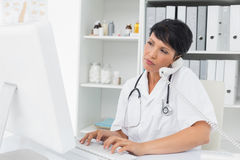 Concentrated doctor using computer and telephone Royalty Free Stock Photo