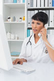 Concentrated doctor using computer and telephone Stock Photography