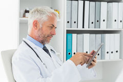 Concentrated doctor using digital tablet at medical office Stock Images