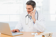 Concentrated doctor using laptop and phone Royalty Free Stock Photo