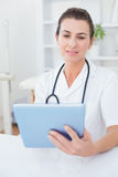 Concentrated doctor using tablet pc Stock Images