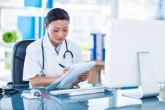 Concentrated doctor writing on clipboard. In medical office Stock Photos