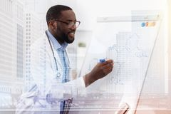 Concentrated doctor writing down chemical formula. Development of science. Positive concentrated doctor writing down chemical formula while using a board and Royalty Free Stock Photography