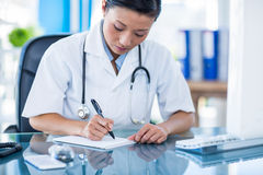 Concentrated doctor writing on notebook Stock Photography