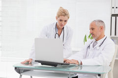 Concentrated doctors coworker using laptop Stock Photo