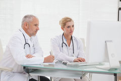 Concentrated doctors coworker using laptop. In medical office Royalty Free Stock Photos