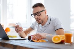 Concentrated earnest man taking biohacking supplements. Biohack your life. Handsome progressive doubtful man deciding about biohacking supplements while sitting Stock Photography