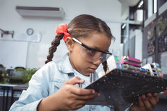 Concentrated elementary student examining circuit board Royalty Free Stock Images