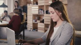 Concentrated European young girl typing a letter on laptop. Hard work in trendy office space, teamwork in background 4K. stock footage