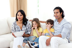 Concentrated family watching TV on sofa. In the living room Stock Photo