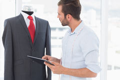 Concentrated fashion designer with digital tablet looking at suit on dummy. Concentrated young male fashion designer with digital tablet looking at suit on dummy Stock Photography