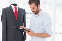 Concentrated fashion designer looking at digital tablet by suit on dummy. Concentrated young male fashion designer looking at digital tablet by suit on dummy in Stock Photography