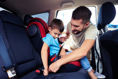 Concentrated father helps his son to fasten belt on car seat Royalty Free Stock Photos