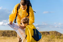 Concentrated father and son reading map during travel. Here is our location. Confident men is pointing finger on map while standing on field. Boy is looking at Stock Photo