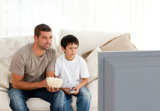 Concentrated father and son watching television stock photography