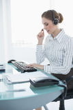 Concentrated female agent sitting at her desk wearing headset Royalty Free Stock Images