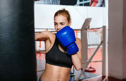 Concentrated female boxer training. Powerful kick. Intent athletic blonde woman in a gym working on her punch with a punch bag while being very serious Stock Photo