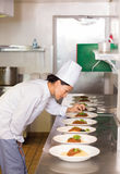 Concentrated female chef garnishing food in kitchen. Side view of a concentrated female chef garnishing food in the kitchen stock photography