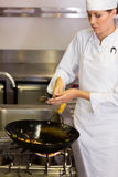 Concentrated female chef preparing food in kitchen Royalty Free Stock Photography