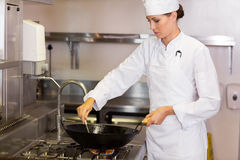 Concentrated female chef preparing food in kitchen. Side view of a concentrated female chef preparing food in the kitchen stock photo