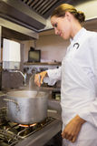 Concentrated female cook preparing food in kitchen. Side view of a concentrated female cook preparing food in the kitchen royalty free stock images