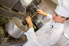 Concentrated female cook preparing food in kitchen Royalty Free Stock Image