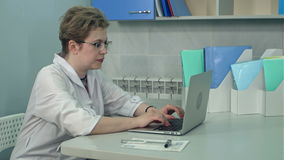 Concentrated female doctor in glasses typing on laptop in her office. Professional shot in 4K resolution. 097. You can use it e.g. in your commercial video stock footage