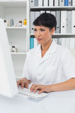 Concentrated female doctor using computer Royalty Free Stock Image