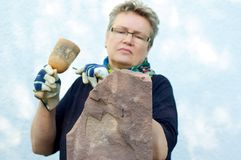 Concentrated female stonemason. Woman is processing a stone Royalty Free Stock Photos