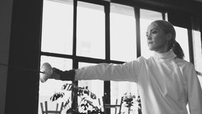 Young concentrated fencer woman training fencing exercise in studio indoors. Concentrated fencer woman training fencing defence exercise in studio indoors Stock Image