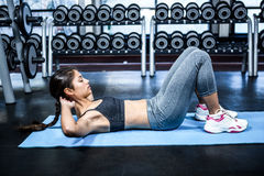 Concentrated fit woman doing sit ups. At gym Stock Photo